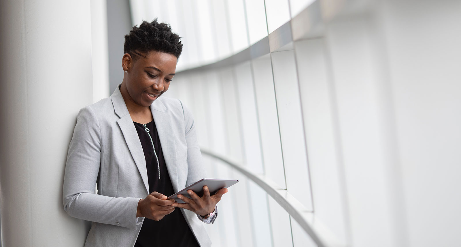 Trendy black business woman, grey suit, working on tablet, happy in office